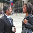 Businessman and businesswoman talk in the street before shaking hands. — Stock video