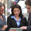 Group of business colleagues stand in street using a digital tablet. - Stock Photo