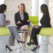 Stock Video: Three businesswomen sit and have informal meeting discussing report together.