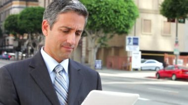 Businessman standing in street using a digital tablet. — Stock Video