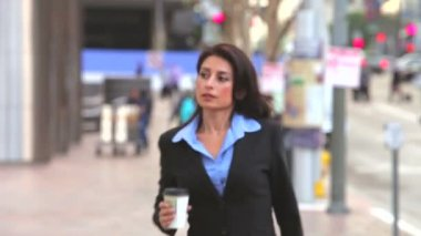 Businesswoman holding cup of takeaway coffee walks into and then out of frame. — Stock Video