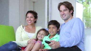 Family of four sitting on sofa — Stockvideo