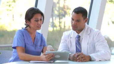 Doctor and nurse sitting at table and dicussing data on digital tablet. — Stock Video