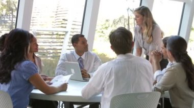 Businesswoman standing and addressing group to colleagues seated and listening. — Stock Video