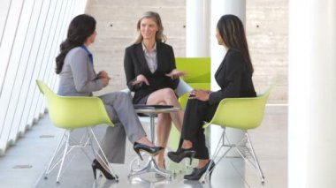 Three businesswomen sit and have informal meeting discussing report together. — Stock Video