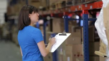 Female worker writes notes on document on clipboard before walking away — Stock Video