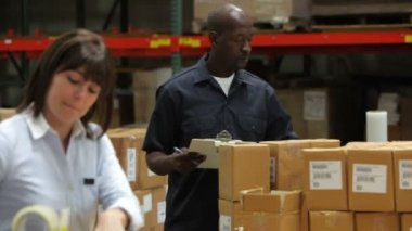 Male factory worker checking boxes against clipboard and female colleague is sealing packages for dispatch. — Stock Video
