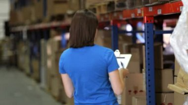 Female worker walks into frame, takes box from shelf and writes on clipboard — Stock Video