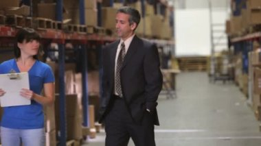 Manager walking in warehouse, talks with worker checking goods on clipboard — Stock Video