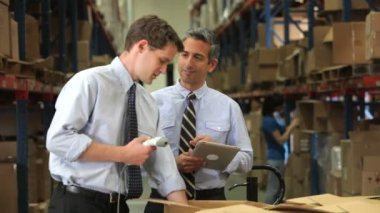 Two businessmen checking contents of boxes using digital tablet and hand held scanner. — Stock Video