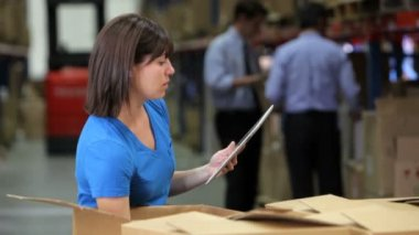 Female worker checks contents of boxes using digital tablet. — Stock Video