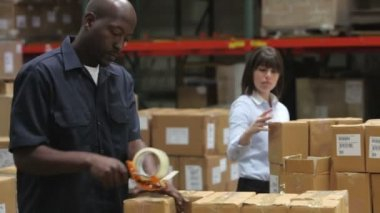 Male factory worker sealing packages for dispatch as female colleague checks boxes against clipboard. — Stock Video