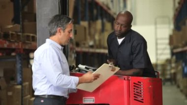 Manger shows fork lift truck driver clipboard with document which they discuss. — Stock Video
