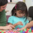 Teacher helping children solve puzzles with blocks. — Vídeo Stock