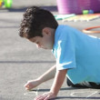 Stock Video: Boy writes name on playground with chalk.