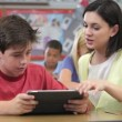 Teacher and student discuss information on tablet computer. — Stock Video #25436147