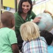 Teacher sitting in chair showing globe to a group of children. — Stock Video #25436229