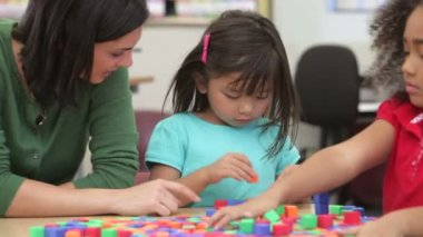 Teacher helping children solve puzzles with blocks. — Stock Video