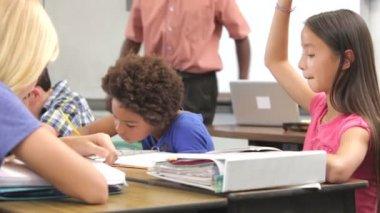 Läraren hjälper eleverna studera vid skrivbord i klassrummet — Stockvideo
