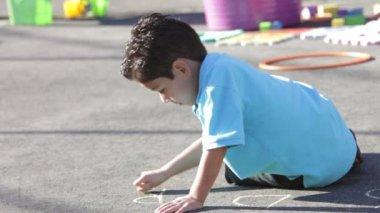 Boy writes name on playground with chalk. — Stock Video