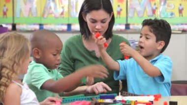 Students sitting at table with teacher using plastic construction set. — Stock Video