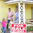 Family Standing By For Sale Sign Outside Home — Stock Video
