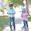Boy And Girl Wearing Safety Helmets And Riding Scooters — Stock Video