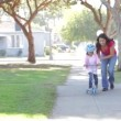 Stock Video: Mother Teaching Daughter To Ride Scooter
