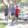 Group Of Male Runners Exercising On Suburban Street — 图库视频影像