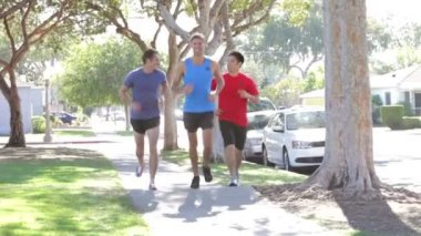 Group Of Male Runners Exercising On Suburban Street — Stock Video