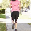 Rear View Of Female Runner Exercising On SuburbStreet — Stock Photo #27552943