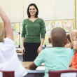 Stock Photo: Teacher Talking To Elementary Pupils In Classroom