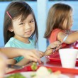 Elementary Pupils Enjoying Healthy Lunch In Cafeteria — Stock Photo #27552987