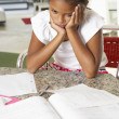 Foto Stock: Fed Up Girl Doing Homework In Kitchen