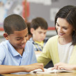 Teacher Reading With Male Pupil In Class — Stock Photo