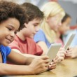Stock Photo: Pupils In Class Using Digital Tablet