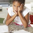 Stock Photo: Fed Up Girl Doing Homework In Kitchen