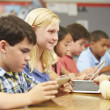 Pupils In Class Using Digital Tablet With Teacher — Stock Photo #27553647