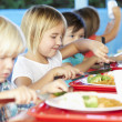 Elementary Pupils Enjoying Healthy Lunch In Cafeteria — Stock Photo #27553721