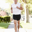 Male Runner Exercising On SuburbStreet — Stock Photo #27553749