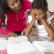 Mother Helping Daughter With Homework In Kitchen — Stock Photo #27553759