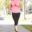 Stock Photo: Female Runner Exercising On SuburbStreet