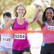 Stock Photo: Two Female Runners Finishing Race Together