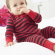 Stock Photo: Toddler Sitting On Bed Wearing Pajamas