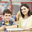 Teacher Helping Pupils Studying At Desks In Classroom — Stock Photo #27553897