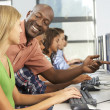 Teacher Helping Students Working At Computers In Classroom — Stock Photo #27553905