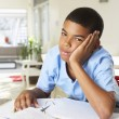 Foto Stock: Fed Up Boy Doing Homework In Kitchen