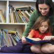 Elementary Pupil Reading With Teacher In Classroom — Stock Photo #27553955