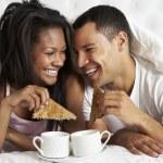 Desayuno disfrutando de pareja en la cama — Foto de Stock
