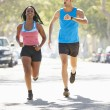 Stock Photo: WomRunning Along Street With Personal Trainer